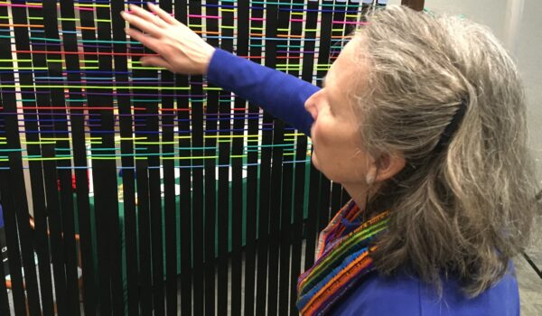 Social Fabric DNA founder Geralyn Sparough with social fabric weaving panel